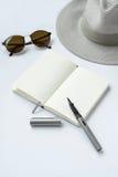 Lunettes de soleil, carnet, stylo, et chapeau, sur le fond blanc Photos libres de droits