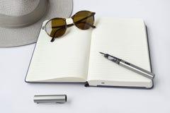 Lunettes de soleil, carnet, stylo, et chapeau, sur le fond blanc Photos stock