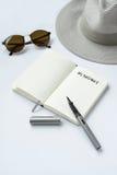 Lunettes de soleil, carnet, stylo, et chapeau, sur le fond blanc Photo stock