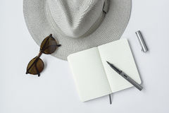 Lunettes de soleil, carnet, stylo, et chapeau, sur le fond blanc Photo libre de droits