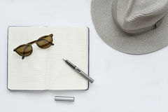 Lunettes de soleil, carnet, stylo, et chapeau, sur le fond blanc Image stock