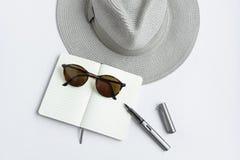 Lunettes de soleil, carnet, stylo, et chapeau, sur le fond blanc Images stock