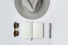 Lunettes de soleil, carnet, stylo, et chapeau, sur le fond blanc Images libres de droits