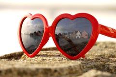 Lunettes de soleil de fantaisie reflétant les maisons types d'île Photos stock