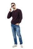 Lunettes de soleil de port d'homme heureux sûr parlant au téléphone regardant l'appareil-photo Photographie stock libre de droits