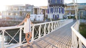 Lunettes de soleil de port de belle femme regardant l'appareil-photo se tenant sur le pont Photo stock