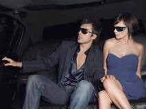 Lunettes de soleil de port de couples dans la limousine Photographie stock libre de droits