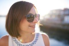 Lunettes de soleil de port de femme de brune et sourire heureusement Images stock