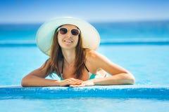 Lunettes de soleil de port de femme heureuse avec le chapeau blanc Photographie stock libre de droits