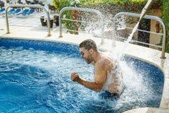 Lunettes de soleil de port de jeune homme bel appréciant le jet de l'eau Photos libres de droits