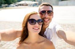 Lunettes de soleil de port de sourire de couples faisant le selfie Images libres de droits