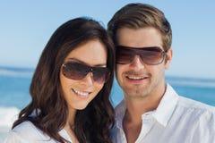 Lunettes de soleil de port de sourire et regarder de couples l'appareil-photo Photographie stock libre de droits