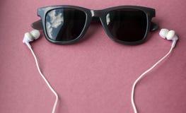 Lunettes de soleil et écouteurs sur le fond rose en pastel photos stock