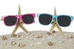 Lunettes de soleil et étoiles de mer sur le sable de plage Photographie stock