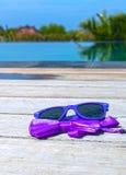 Lunettes de soleil et noeud papillon près de la piscine photos stock