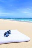 Lunettes de soleil et serviette sur la plage sablonneuse blanche tropicale Image libre de droits