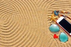 Lunettes de soleil et smartphone sur la plage Photographie stock libre de droits
