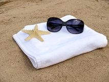 Lunettes de soleil et étoiles de mer sur l'essuie-main blanc Photographie stock libre de droits