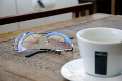 Lunettes de soleil et une cuvette de café Photos libres de droits