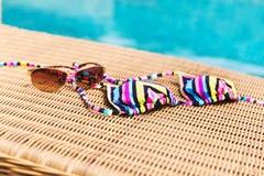 Lunettes de soleil et vêtements de bain près de piscine Photographie stock libre de droits