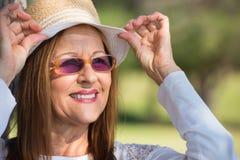 Lunettes de soleil heureuses de femme et jour ensoleillé de chapeau Photo libre de droits