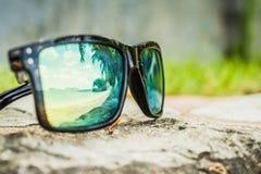 Lunettes de soleil ? la mode Lunettes de soleil avec les lentilles refl?t?es R?flexion de la plage et des palmiers tropicaux dans images stock
