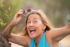 Lunettes de soleil mûres de sourire joyeuses de femme extérieures Images stock
