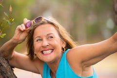 Lunettes de soleil mûres sûres joyeuses de femme extérieures Image stock