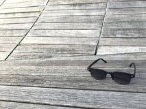 Lunettes de soleil mises sur le banc en bois de panneau de couleur naturelle élégante Photo stock