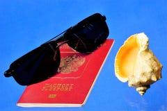 Lunettes de soleil, passeport russe et coquillage Un voyage dans la plage un monde de relaxation images stock