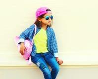 Lunettes de soleil de port d'enfant de petite fille de mode, casquette de baseball, sac à dos sur la rue de ville sur le blanc photos stock