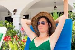 Lunettes de soleil de port et chapeau de belle femme caucasienne détendant sur un lit pliant dans une station de vacances images libres de droits
