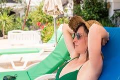 Lunettes de soleil de port et chapeau de belle femme caucasienne détendant sur un lit pliant dans une station de vacances photos stock