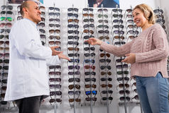 Lunettes de soleil proches blondes mûres de consultation d'affichage de vendeur d'optométriste de client Images stock