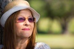 Lunettes de soleil réfléchies de femme et jour ensoleillé de chapeau Photos stock