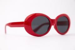 Lunettes de soleil rondes rouges mignonnes sur le fond blanc Photographie stock libre de droits