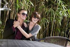 Lunettes de soleil s'usantes de jeunes couples heureux sur le patio photographie stock