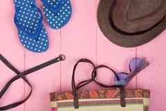 lunettes de soleil, sac de plage de paille, chapeau du soleil, ceinture et bascules électroniques sur la table en bois rose Photos libres de droits