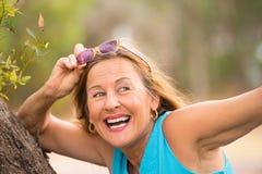Lunettes de soleil supérieures de sourire joyeuses de femme extérieures Image stock