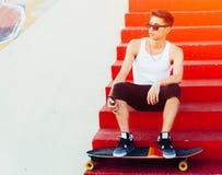 Lunettes de soleil urbaines et longboard d'homme posant sur les escaliers rouges Type frais Chemise blanche de port et pantalon n Photos libres de droits