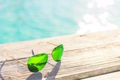 Lunettes de soleil vertes sur une plate-forme en bois, concept de vacances d'été Photos libres de droits