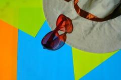 Lunettes de Sun, chapeau sur le fond bleu et jaune image libre de droits