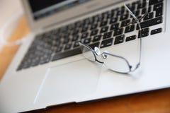 Lunettes sur le clavier d'ordinateur portable Photographie stock