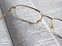Lunettes sur un dictionnaire Image stock