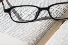 Lunettes sur un vieux livre ouvert Photo stock