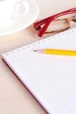 Lunettes, un cahier et une tasse de thé images libres de droits