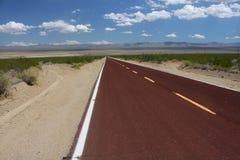 Lunga strada attraverso il deserto di Mojave Fotografie Stock