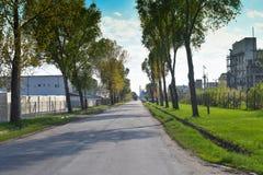 Lunga strada nella zona industriale vicino allo stabilimento chimico La natura sta provando a resistere a l? immagini stock libere da diritti