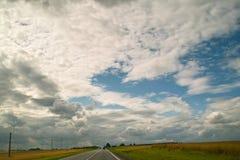 Lunga strada sotto le nuvole Immagine Stock
