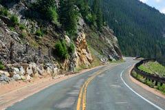 Lungamente e strada Curvy d'avvolgimento della montagna con la recinzione della frana di roccia Immagini Stock